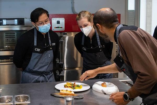 Dos alumnos y un profesor dando feedback de la evaluación de aprendizajes del Culinary Institute of Barcelona